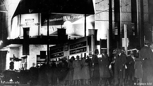 A black-and-white photo of a crowd in front of the Titania Palast cinema in Berlin.