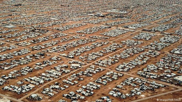 An aerial picture of a gridded city of tents extending into the distance