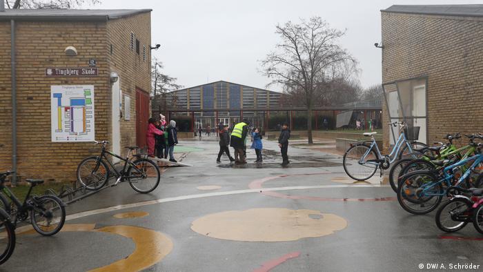 Kinder und Aufpasser auf dem Spielplatz vor der Tingbjerg Schule