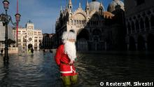 23.12.2019 *** A man dressed as Santa Claus wades through floodwater in St. Mark's Square during high tide in Venice, Italy, December 23, 2019. REUTERS/Manuel Silvestri TPX IMAGES OF THE DAY