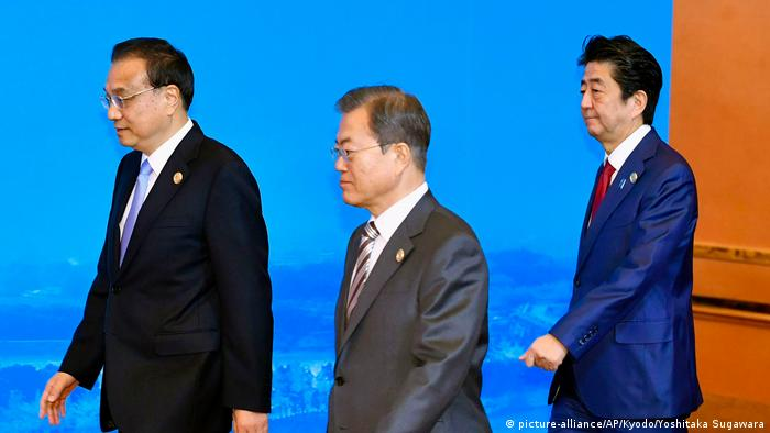 Chinese Premier Li Keqiang, left, South Korean President Moon Jae-in, center, and Japan's Prime Minister Shinzo Abe, right, walk to a group photo session