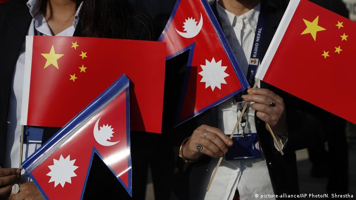 Government officers hold Chinese and Nepalese flag as they wait to welcome Chinese President Xi Jinping in Kathmandu