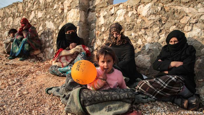 نازحون سوريون من جنوب إدلب يجلسون في المناطق الريفية الواقعة غرب الريف من مدينة دانا في المنطقة الشمالية الغربية من سوريا في 23 ديسمبر/ كانون الأول.