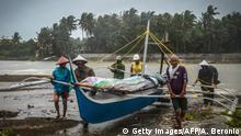 Philippinen | Fischer tragen ein Boot in Sicherheit bevor der Taifun Phanfone Land erreicht