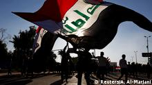 Iraqi demonstrators carry the Iraqi flag during ongoing anti-government protests in Najaf, Iraq December 20, 2019. REUTERS/Alaa al-Marjani