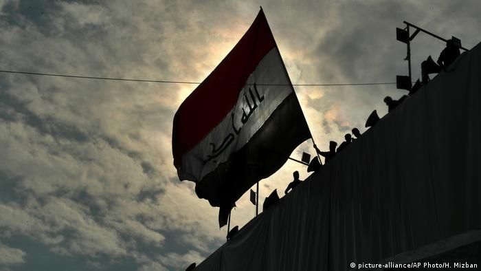Anti-government protesters wave a flag while standing on a building near Tahrir Square during ongoing protests in Baghdad
