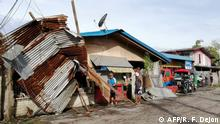 Residents stand next to a house damaged by typhoon Phanfone in Ormoc City, Leyte province in central Philippines on December 25, 2019. - Typhoon Phanfone pummelled the central Philippines on December 25, bringing a wet, miserable and terrifying holiday season to millions in the mainly Catholic nation. (Photo by RONALD FRANK DEJON / AFP)