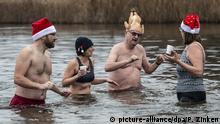 25.12.2019, Berlin: Teilnehmer am Weihnachtsschwimmen des Vereins Berliner Seehunde stehen im Orankesee. Foto: Paul Zinken/dpa | Verwendung weltweit