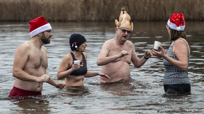 People having a drink in the river with Santa hats