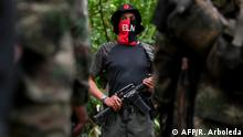 Commander Uriel of the Ernesto Che Guevara front, belonging to the National Liberation Army (ELN) guerrillas, gives instructions to his men at the jungle, in Choco department in Colombia, on May 25, 2019. - Uriel is part of the generational relay of an organization that emerged in 1964, in the middle of the Cold War, and it's led by guerrillas of 68 years old average. He is also the most connected leader to social networks - despite the official hunt of him and his accounts on Twitter, Instagram and Facebook - although he never uncovers his face before the cameras. (Photo by Raul ARBOLEDA / AFP) (Photo credit should read RAUL ARBOLEDA/AFP via Getty Images)
