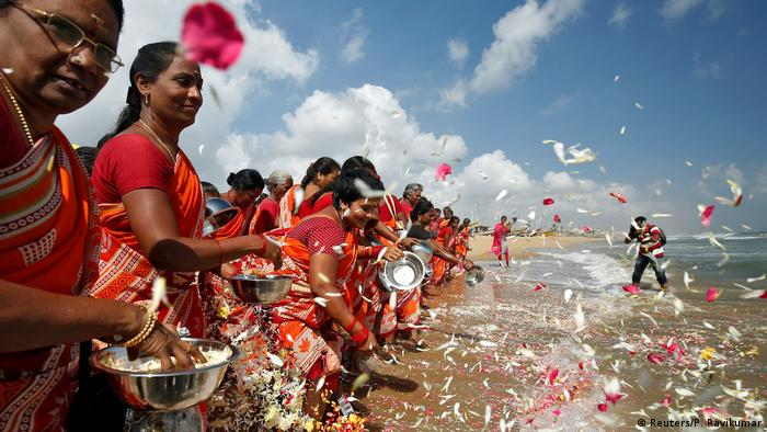 Women scatter flower petals in the waters of the Bay of Bengal during a prayer ceremony for the victims of the 2004 tsunami (Reuters/P. Ravikumar)