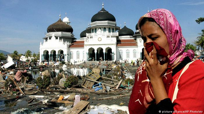 A woman walks near a mosque amid rubbish from the Indian Ocean tsunami in December 2004 (picture-alliance/AP Photo/str)