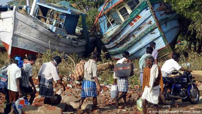 People in the southern Indian state of Tamil Nadu walk past boats that washed ashore during the 2004 tsunami disaster (picture-alliance/AP Photo/G. Singh)