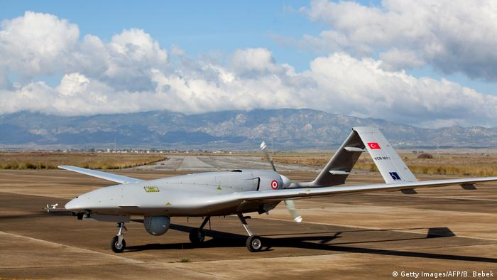 A Turkish Bayraktar TB2 drone sits on a runway with mountains in the background