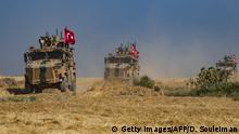 Turkish military vehicles, part of a US military convoy, take part in joint patrol in the Syrian village of al-Hashisha on the outskirts of Tal Abyad town along the border with Turkey, on October 4, 2019. - The United States and Turkey began joint patrols in northeastern Syria aimed at easing tensions between Ankara and US-backed Kurdish forces. (Photo by Delil SOULEIMAN / AFP) (Photo by DELIL SOULEIMAN/AFP via Getty Images)