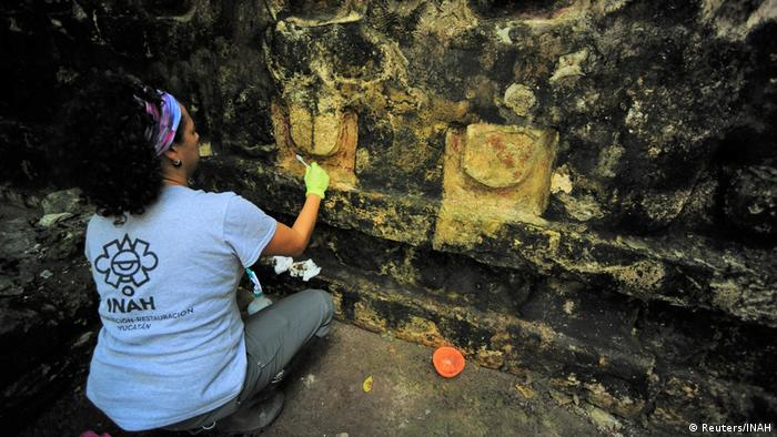 An archaeologist scrapes the wall of the ancient temple