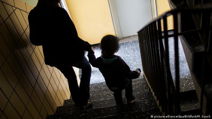 Foto simbólica de un niño bajando las escaleras de la mano de una mujer.