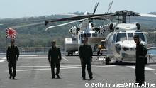 Helicopter crew of Japan's helicopter carrier Ise walk on the deck next to a flag shortly after arriving at the former US naval base, Subic port, north of Manila on April 26, 2016. Ise (DDH 182), which is in the Philippines for a four-day goodwill visit, marking a third time Japanese vessels have visited the country in a year, with two Japanese destroyers and a submarine docked April 3 near disputed South China Sea waters, where Beijing's increasingly assertive behaviour has sparked global concern. / AFP / TED ALJIBE (Photo credit should read TED ALJIBE/AFP via Getty Images)