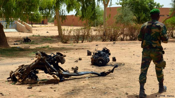 A Nigerian soldier walks by wreckage from a suicide bombing