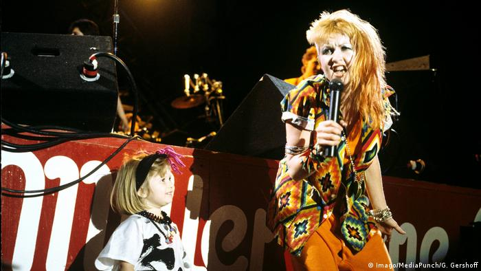 Cyndi Lauper sings in 1984 in a punk outfit into a microphone as a little girl stands next to her (Imago/MediaPunch/G. Gershoff)