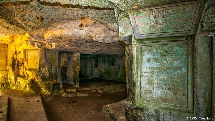 Galeria em túnel com placas de inscrições gravadas em pedra
