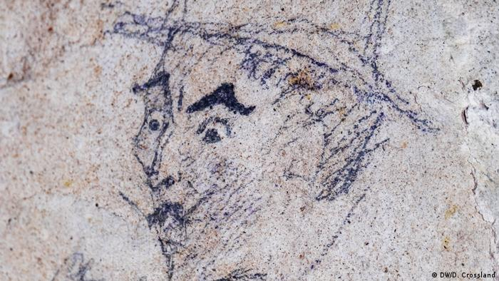 Gravura em pedra de homem com bigode e chapéu