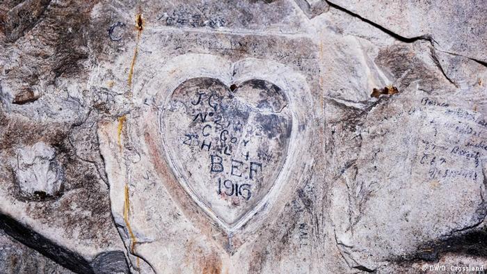 Coração esculpido em pedra com inscrições dentro