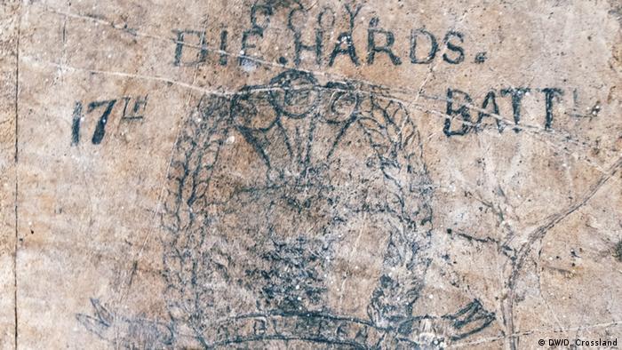 Desenho e inscrição pretos feitos sobre pedra