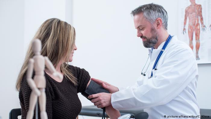 Ein Arzt misst bei einer Patientin den Blutdruck