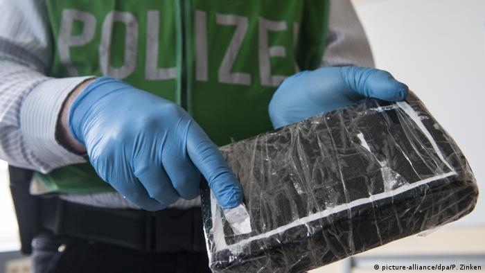 German police officer with a brick of cocaine