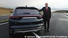 27.12.2019, Türkei, Gebze: Recep Tayyip Erdogan, Präsident der Türkei, steht neben einem Prototypen eines im Inland produzierten Elektroautos. Erdogan hat mit großer Fanfare eine heimische Automarke vorgestellt. Foto: Uncredited/Pool Turkish Presidency/AP/dpa +++ dpa-Bildfunk +++ |