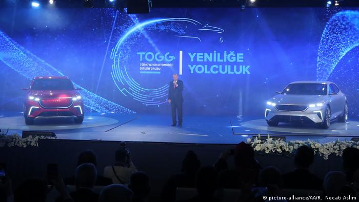 Turkish President Recep Tayyip Erdogan speaks between the Turkey's first indigenous automobile models during the official opening ceremony of the Information Valley technology hub