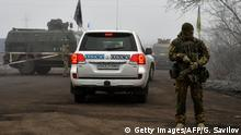 29.12.2019 A car of the Organization for Security and Co-operation in Europe (OSCE) drives past Ukrainian servicemen in the settlement of Odradivka prior to a prisoner exchange between Ukraine and pro-Russian rebels on December 29, 2019. (Photo by GENYA SAVILOV / AFP) (Photo by GENYA SAVILOV/AFP via Getty Images)