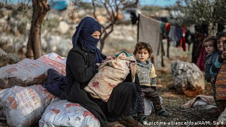A woman sits with her children at a soil field in cold weather at Harbanush village, Idlib. Muhammed Said / Anadolu Agency