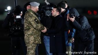 Президент Украины Владимир Зеленский приветствует освобожденных украинских военных