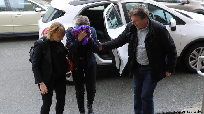 The defendant covers her face as she arrives at the Famagusta court house in Paralimni, Cyprus