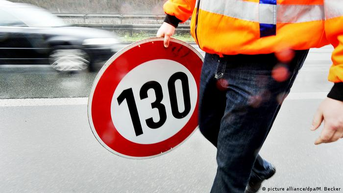 A road worker holds a 130 km/h sign
