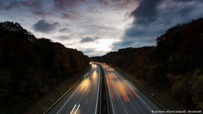 Cars speed along a German highway at dusk