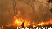 15.12.2019***A firefighters works at the scene of a bushfires in Gospers Mountain, New South Wales, Australia in this still image from a social media video December 15, 2019. Chrys Maoudis/Cottage Point Rural Fire Brigade via REUTERS ATTENTION EDITORS - THIS IMAGE HAS BEEN SUPPLIED BY A THIRD PARTY. MANDATORY CREDIT. NO RESALES. NO ARCHIVES.