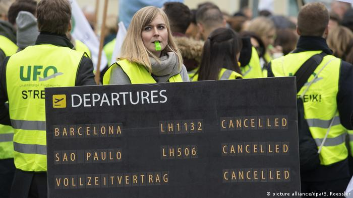 A striking flight attendant holding a sign showing canceled flights