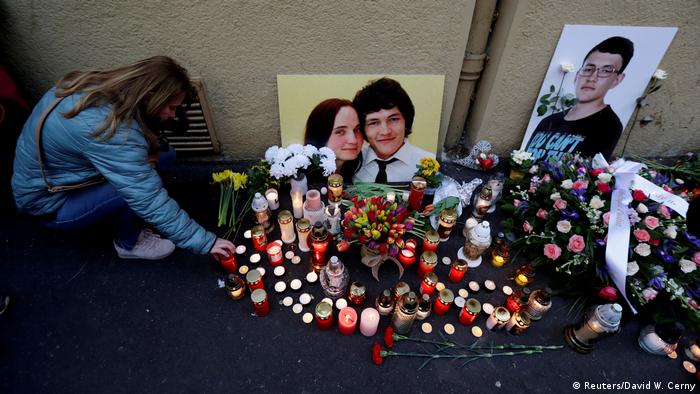 Woman kneeling and placing candle before picture of Jan Kuciak and his fiancee Martin Kusnirovna (Reuters/David W. Cerny)