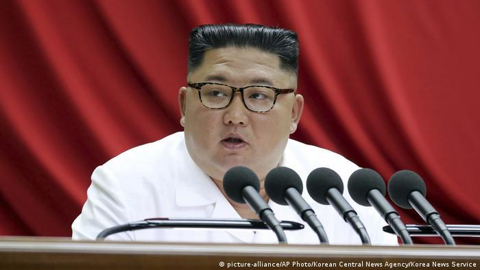 Kim Jong-un fala em frente a microfones e com uma cortina vermelha ao fundo
