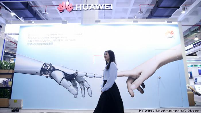 A visitor walks past the stand of Huawei during the International Metro Transit Exhibition in Beijing