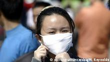 ARCHIV 2004 *** epa00179977 A Chinese woman adjusts a respitory mask she is wearing to protect herself from the threat of SARS (atypical pneumonia) at the Beijing Central Railway Station, Tuesday 27 April 2004. Authorities have quarantined more than 600 people in the capital to prevent another outbreak of the deadly virus as the national holiday Labour Day is fast approaching on 01 May, when millions will be traveling. EPA/MICHAEL REYNOLDS |