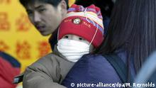 ARCHIV 2004 *** A child wears a respitory mask at the Beijing Central Railway Station, Monday, 12 January 2004. Masks have begun to reappear at crowded public places for fear of a SARS (atypical pneumonia) comeback. Chinese authorities officially announced a second suspected SARS case in the southern city of Guangzhou on Monday, after declaring victory over the virus last summer. SARS has infected over 8,000 people worldwide to date. Foto: Michael Reynolds dpa |