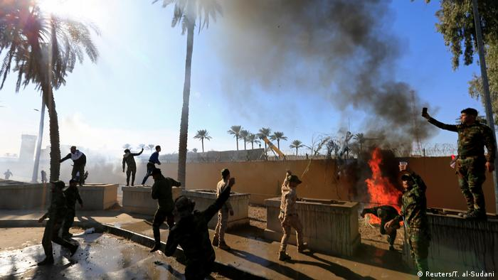 Hashd al-Shaabi (paramilitary forces) fighters set fire on the U.S. Embassy wall to condemn air strikes on their bases