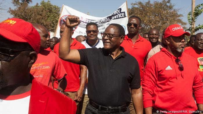 Lazarus Chakwera raises his fist as he walks with protesters in March, 2019.