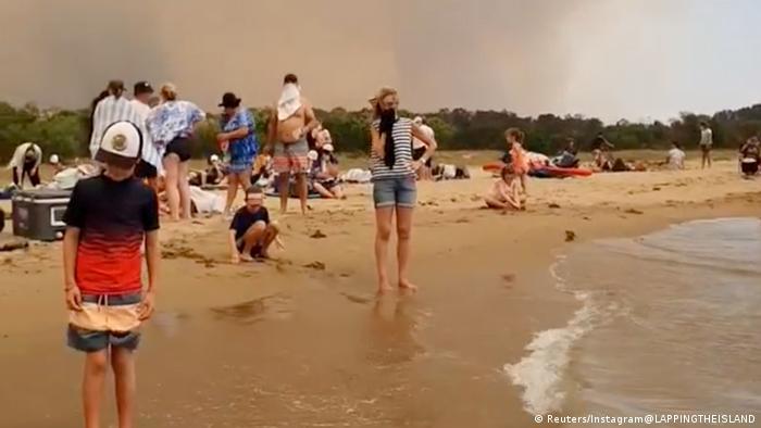 Turistas e moradores na baía de Bateman, no sudeste da Austrália, se refugiam na praia com o avanço das chamas