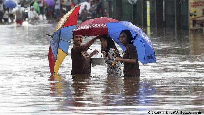People wade through floodwaters at Jatibening on the outskirt of Jakarta