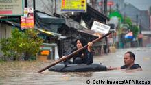 A woman crosses a flooded area in an inflated inner-tube after rain all night caused local flooding in Bekasi, West Java, on January 1, 2020. - Storms, landslides and floods are common in Indonesia during the annual rainy season, which peaks between December and February. (Photo by REZAS / AFP) (Photo by REZAS/AFP via Getty Images)